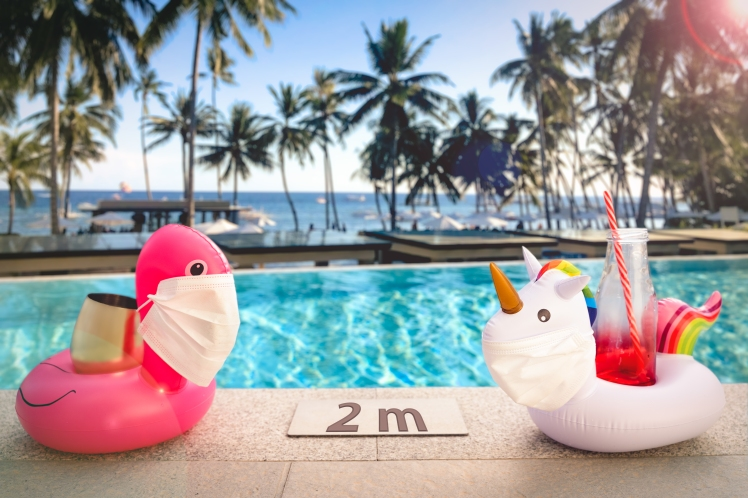 Inflatable pool toys at tropical resort pool wearing face masks staying 2 meters aside to keep social distance during COVID-19 pandemic. Concept of travel industry difficulties during summer 2020